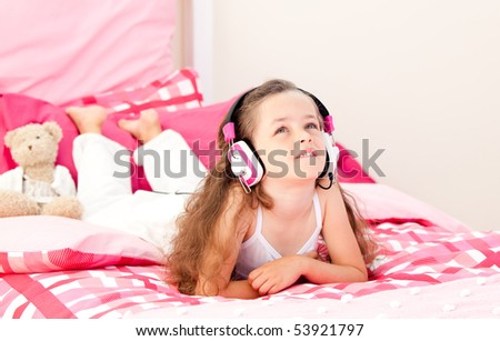Cute little girl listening music lying on her bed at home
