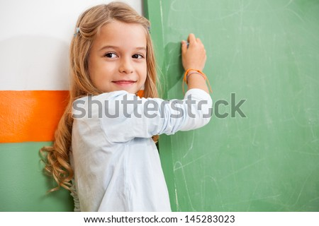 Cute little girl looking away while writing on chalkboard in classroom