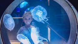 Cute little girl looking over blue jellyfish in aquarium through the glass, medusa in the neon light, underwater life in ocean, Lyon, France, selective focus on medusa