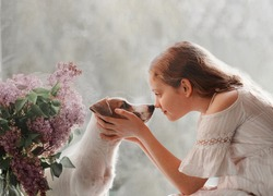 Cute little girl looks into the eyes of a dog. Two friends sitting on the window. Friendship, care, happy childhood concept.