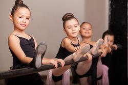 Cute little girl loving her ballet class and raising her leg on a ballet barre