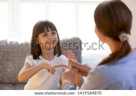 Cute little girl make hand gesture learning sign language with mom or female nanny, smiling small kid practice nonverbal talk with teacher at home, preschooler disabled child have lesson with tutor