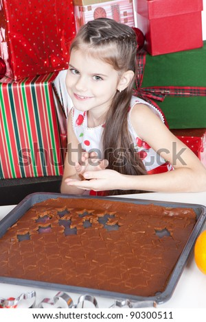 Cute little girl making Christmas cookies at a table
