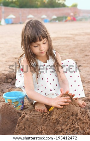 Cute little girl making sand castle on river beach. Femininity concept