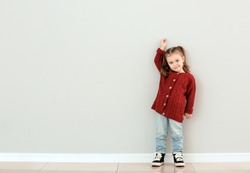 Cute little girl measuring height near grey wall
