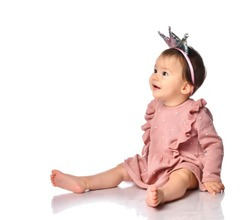 Cute little girl of mixed Caucasian and Asian nationality sits barefoot on a gray background. Child dressed in a dress and a hoop with a crown looks at the free space for text or promotional items.