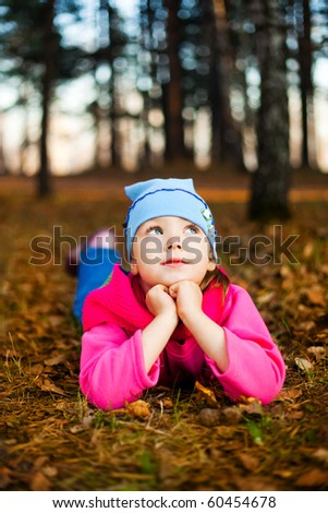 cute little girl on the grass in the autumn park