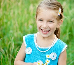 Cute little girl  on the meadow in spring day