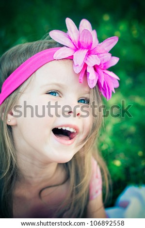 Cute little girl on the meadow laughing