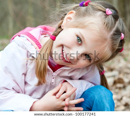 Cute little girl  on the wood in spring day