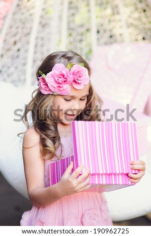 Cute little girl open her birthday gift box