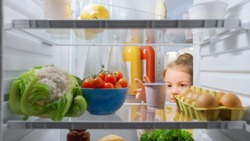 Cute Little Girl Opens Fridge Door, Looks inside Takes out Healthy Yogurt. Smart Little Child Eats Healthy. Shot from Inside the Fridge. Point of View POV Shot from Refrigerator full of Good Food