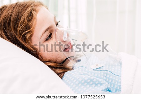 Cute little girl oxygen mask on her face on bed in the hospital #1077525653
