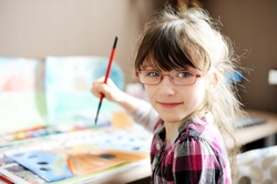 Cute little girl painting a picture in home studio