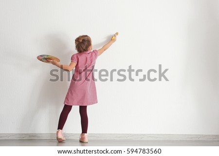Cute little girl painting on wall in empty room #594783560