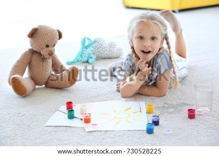 Cute little girl painting picture and spilled water on carpet