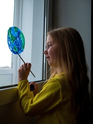 Cute little girl painting planet on window at home. Happy Earth Day April 22 greeting message. Creative family leisure lockdown new reality. Ecology Saving environment conscious consumption concept.