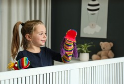 Cute little girl performing puppet show at home