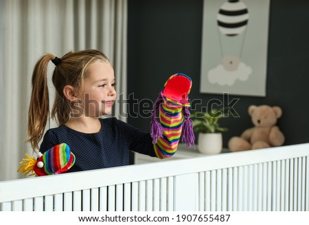 Cute little girl performing puppet show at home Foto stock ©