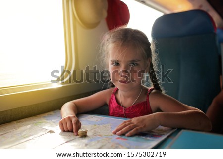 Cute little girl planning her economy vacations during travelling time by train, transport, happy family vacation and summertime, lifestyle inside portrait