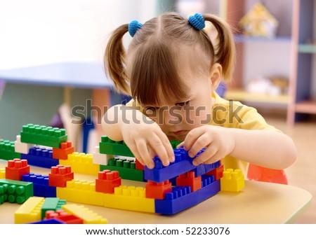 Cute little girl play with building bricks in preschool