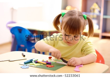 Cute little girl play with plasticine in preschool