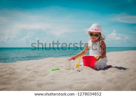 cute little girl play with sand on beach #1278034852