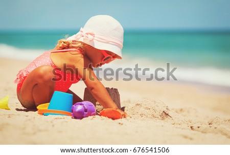 cute little girl play with sand on beach #676541506