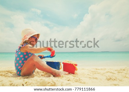 cute little girl play with sand on beach #779111866