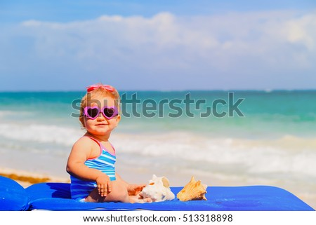 cute little girl play with seashells on beach