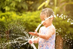 Cute little girl playing a rubber hose spraying water with sunlight in the backyard. Children enjoy outdoor activities on hot summer days.