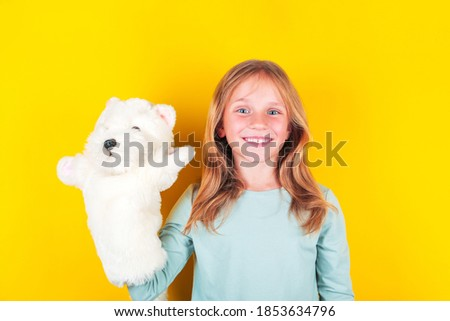 Cute little girl playing dolls theatre , holding fluffy white puppy in hand. Girl playing with glove puppets. Foto stock ©