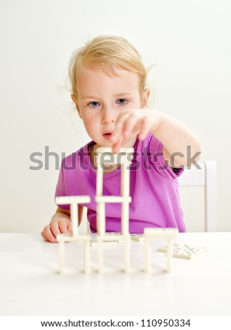 Cute little girl playing domino at the table