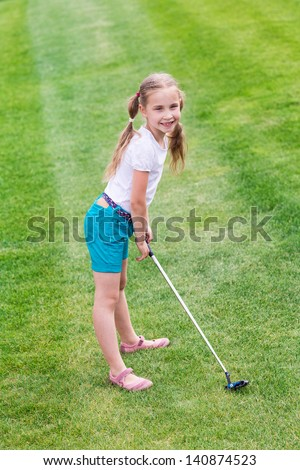 Cute little girl playing golf on a field outdoor