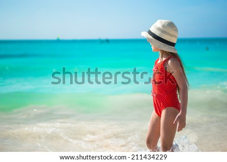 Cute little girl playing in shallow water at exotic beach #211434229