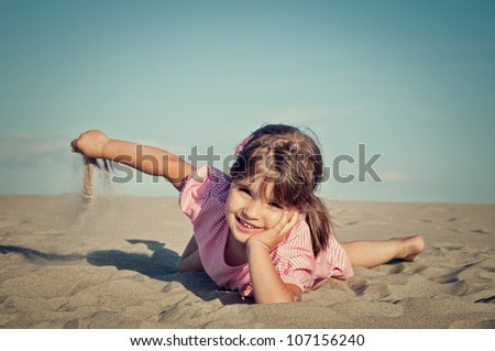 Cute little girl playing in the sand