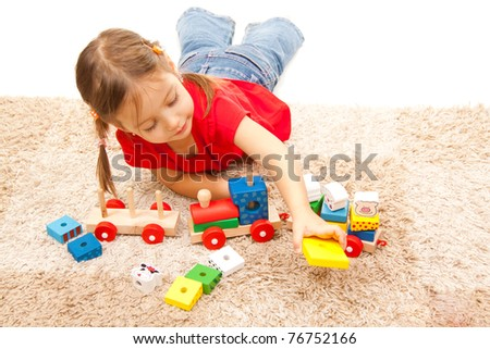 Cute little girl playing on the floor - stock photo