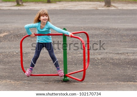 Cute little girl playing on the playground on beautiful spring day.