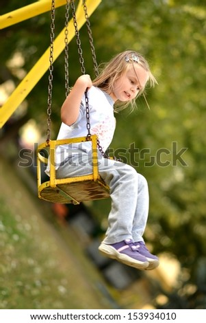 Cute little girl playing on the swing