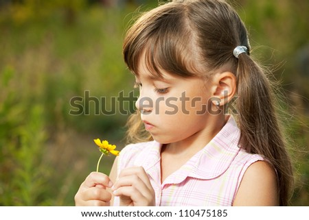 Cute little girl playing with a yellow flower