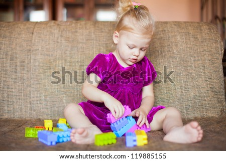 Cute little girl playing with blocks on the couch. Series.