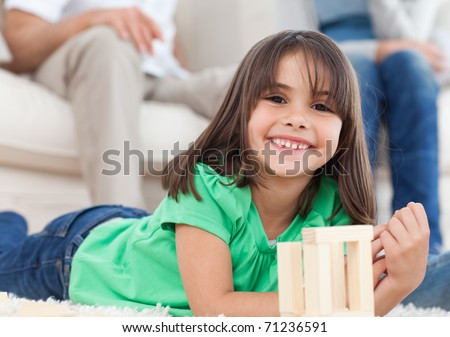Cute little girl playing with dominoes in the living room with her parents