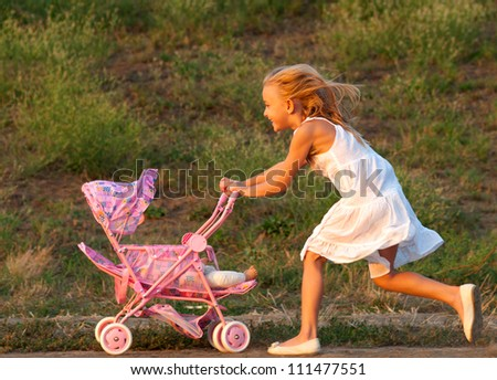 Cute little girl playing with her baby toy on the meadow on sunny summer day.