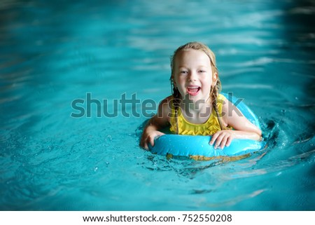 Cute little girl playing with inflatable ring in indoor pool. Child learning to swim. Kid having fun with water toys. Family fun in a pool.