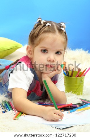 cute little girl playing with multicolor pencils, on blue background