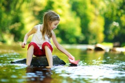 Cute little girl playing with paper boat by a river on warm and sunny summer day