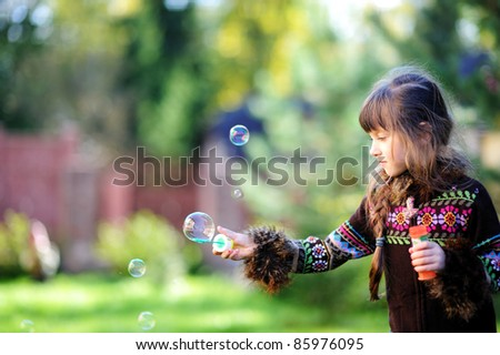 Cute little girl playing with soap bubbles outdoors