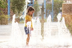 Cute little girl playing with water in fountain on the street in La Mer Beach in Dubai