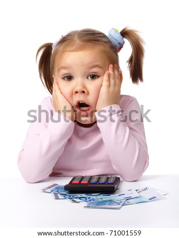 Cute little girl plays with money, holding her face in shock, isolated over white