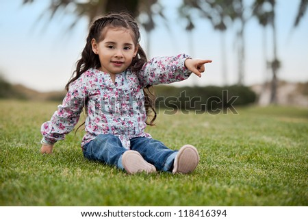 Cute little girl pointing at something